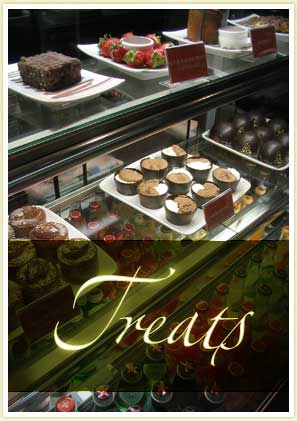 image shows a display case full of treats: cakes, tarts, cold drinks, pies etc.